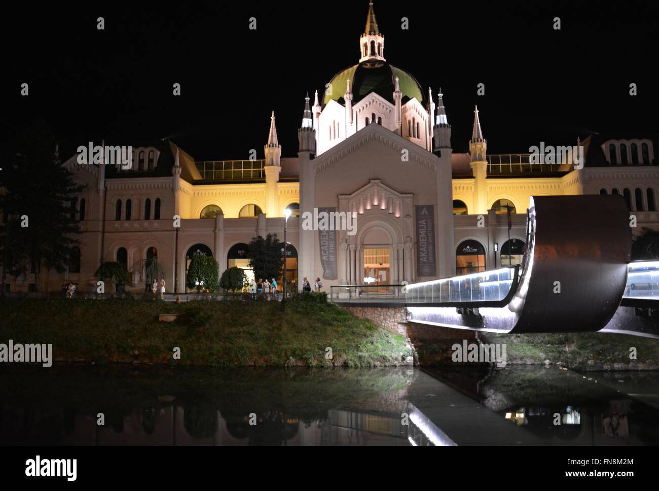 El festina lente puente sobre el río Miljacka conduce a la academia de bellas artes en la noche en Sarajevo, Imagen De Stock