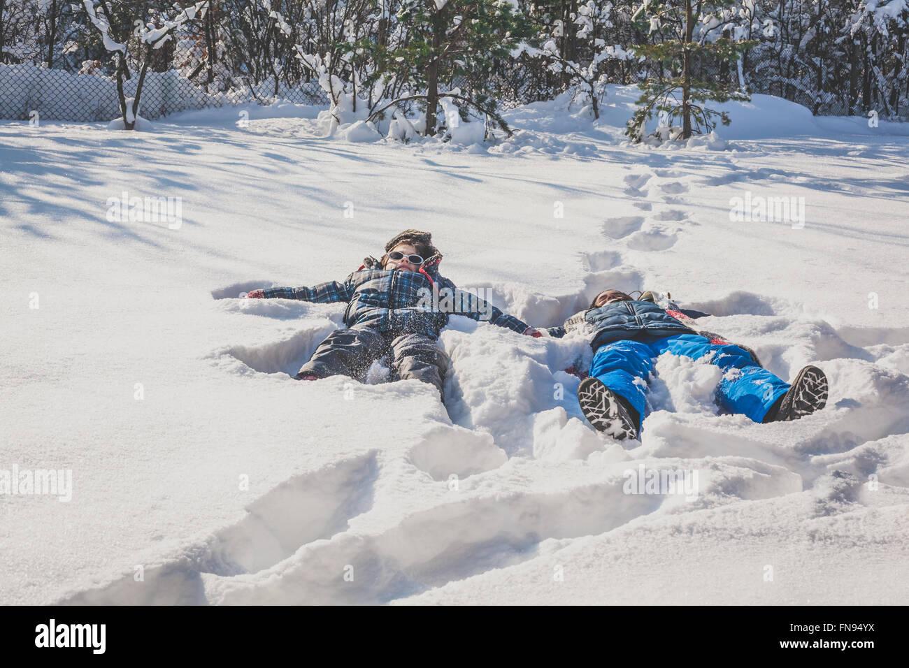 Chico y chica acostada en la nieve haciendo ángeles de nieve en la nieve. Imagen De Stock