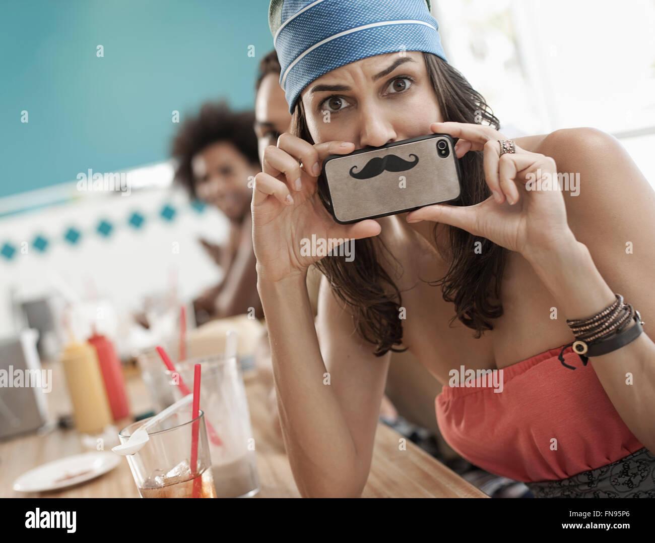 Una mujer sostiene una fotografía de un bigote en su teléfono inteligente justo debajo de su nariz. Imagen De Stock