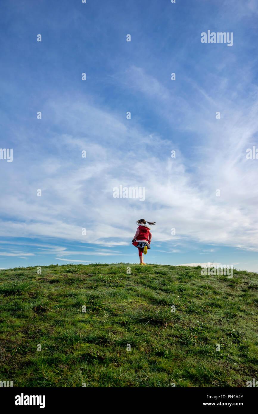 Chica en una colina girando en torno a Foto de stock