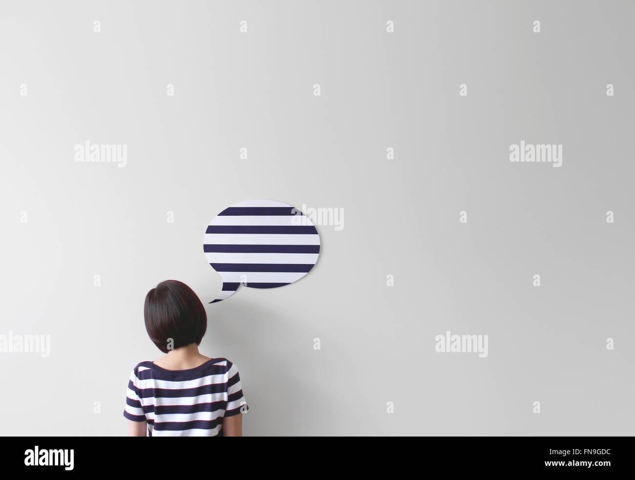 Vista trasera de una mujer en la parte superior con una stripey stripey burbujas de voz Imagen De Stock
