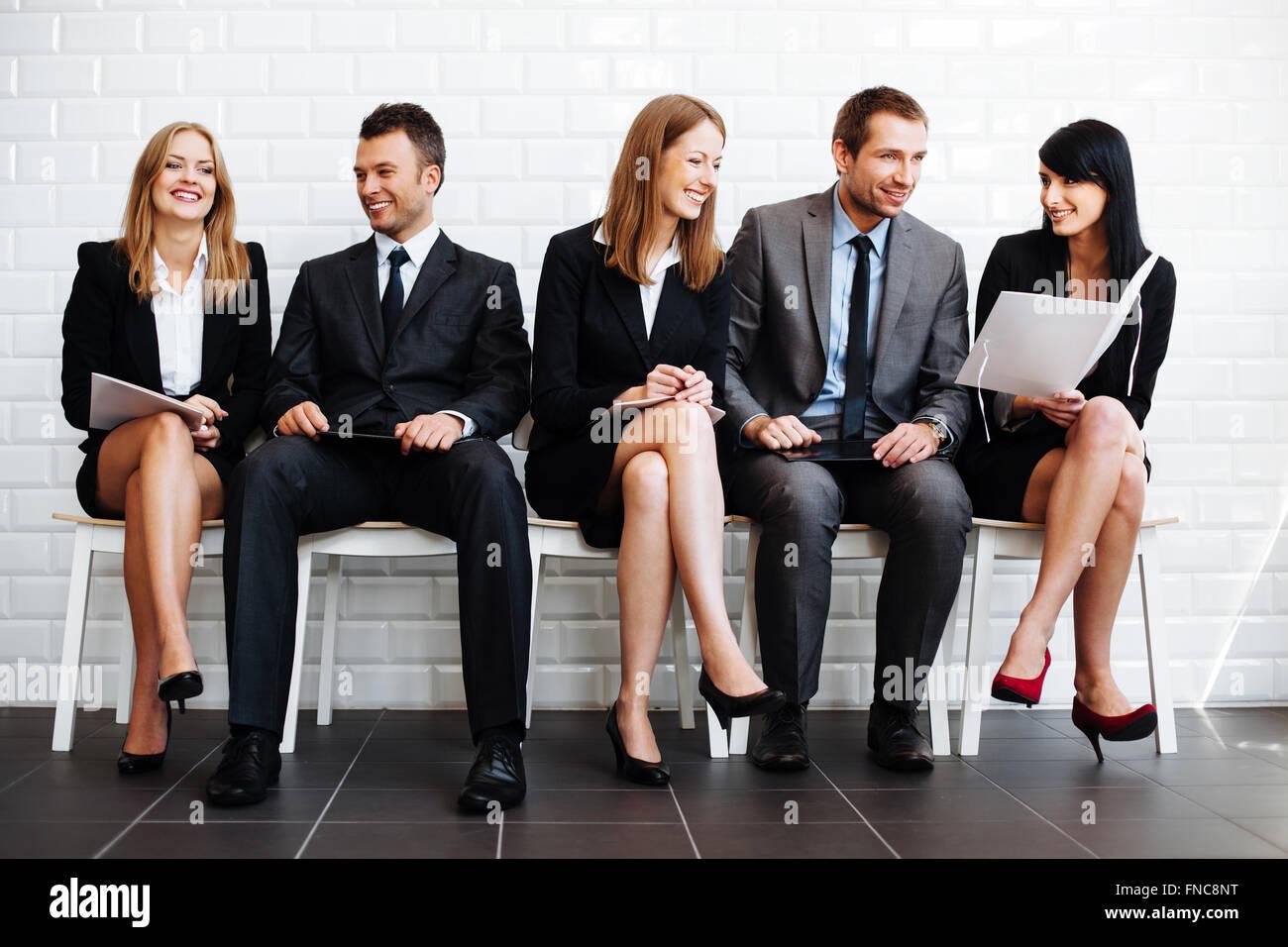Grupo de gente de negocios feliz sentado en la sala de espera. Imagen De Stock
