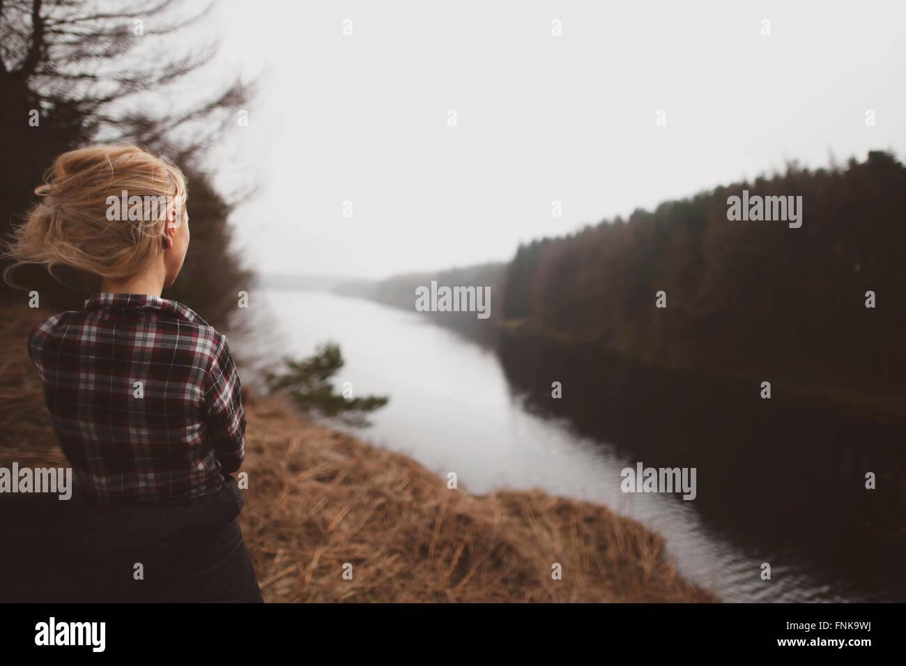Mujer joven de pie sobre la colina, admirando la bella vista Foto de stock