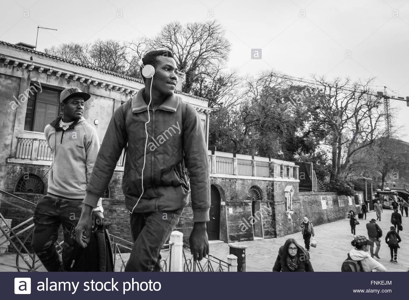 Venecia, Italia - 30 de marzo de 2015: el hombre caminando por Venecia usando audífonos, escuchando música. Imagen De Stock