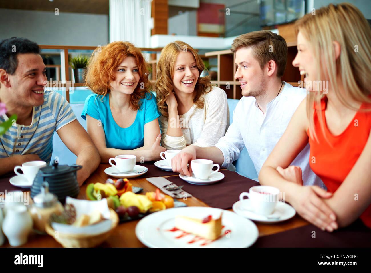 Feliz de tener amigos adolescentes hablar por taza de té en el café Imagen De Stock