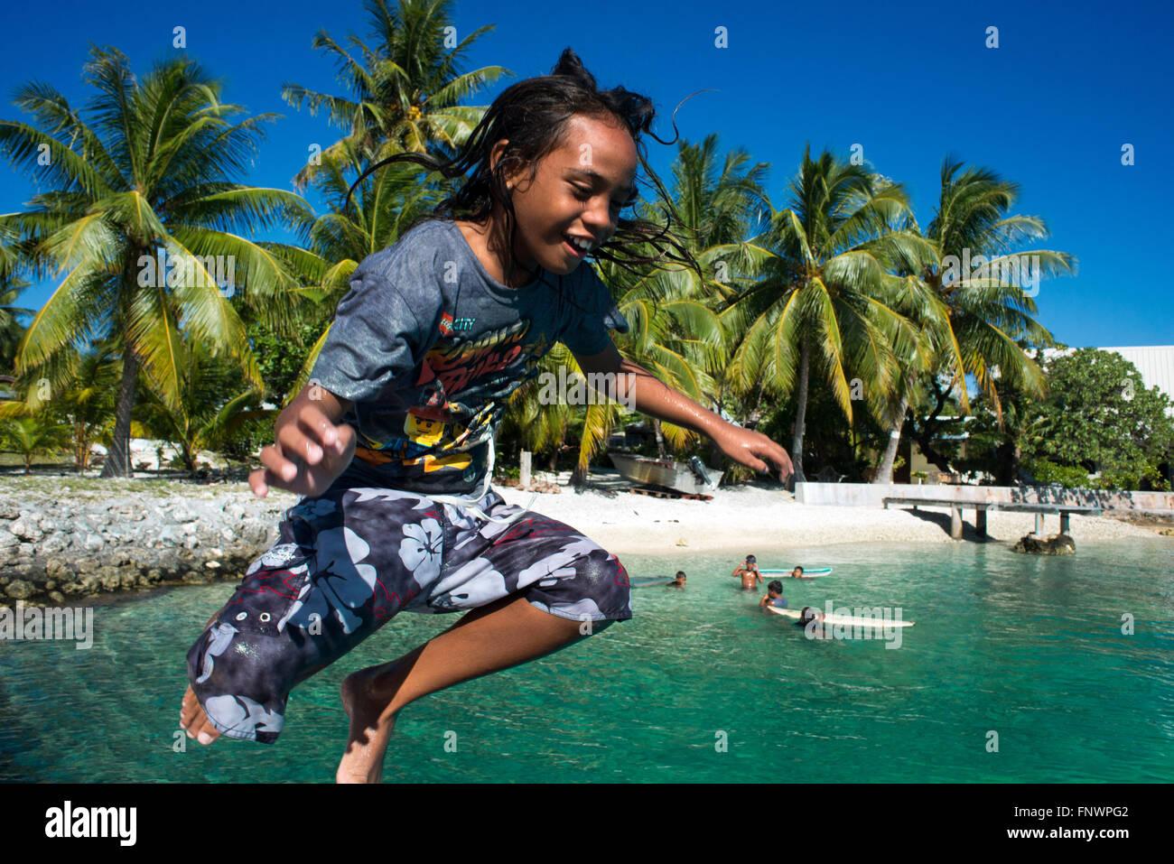 Playa de Rangiroa, las Islas Tuamotu, en la Polinesia Francesa, el Pacífico Sur. Un niño jugando y saltando en el agua. Foto de stock