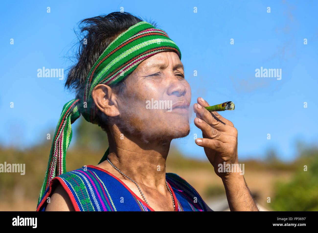 Hombre con traje tradicional de fumar cigarro, Phnong tribu, minoría étnica Pnong, Bunong, Senmonorom, Imagen De Stock