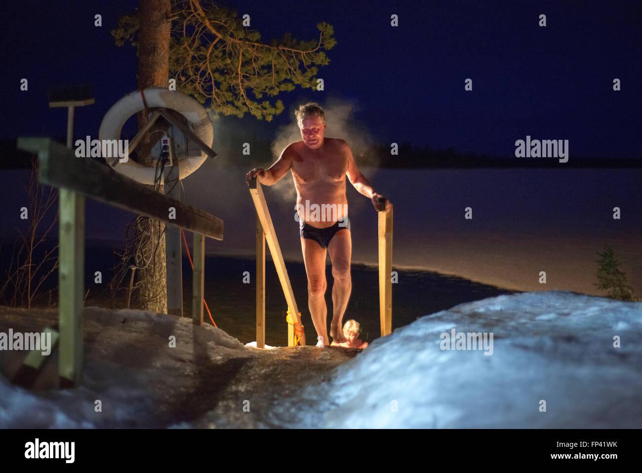 La gente toma un sauna en una cabaña junto al río Kemi, Salla, Laponia, Finlandia. Impresionante experiencia de sauna. Una Saun finlandés Foto de stock
