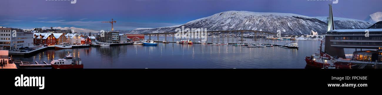 Una vista del puerto, con edificios a un lado y las montañas cubiertas de nieve en el fondo. Imagen De Stock