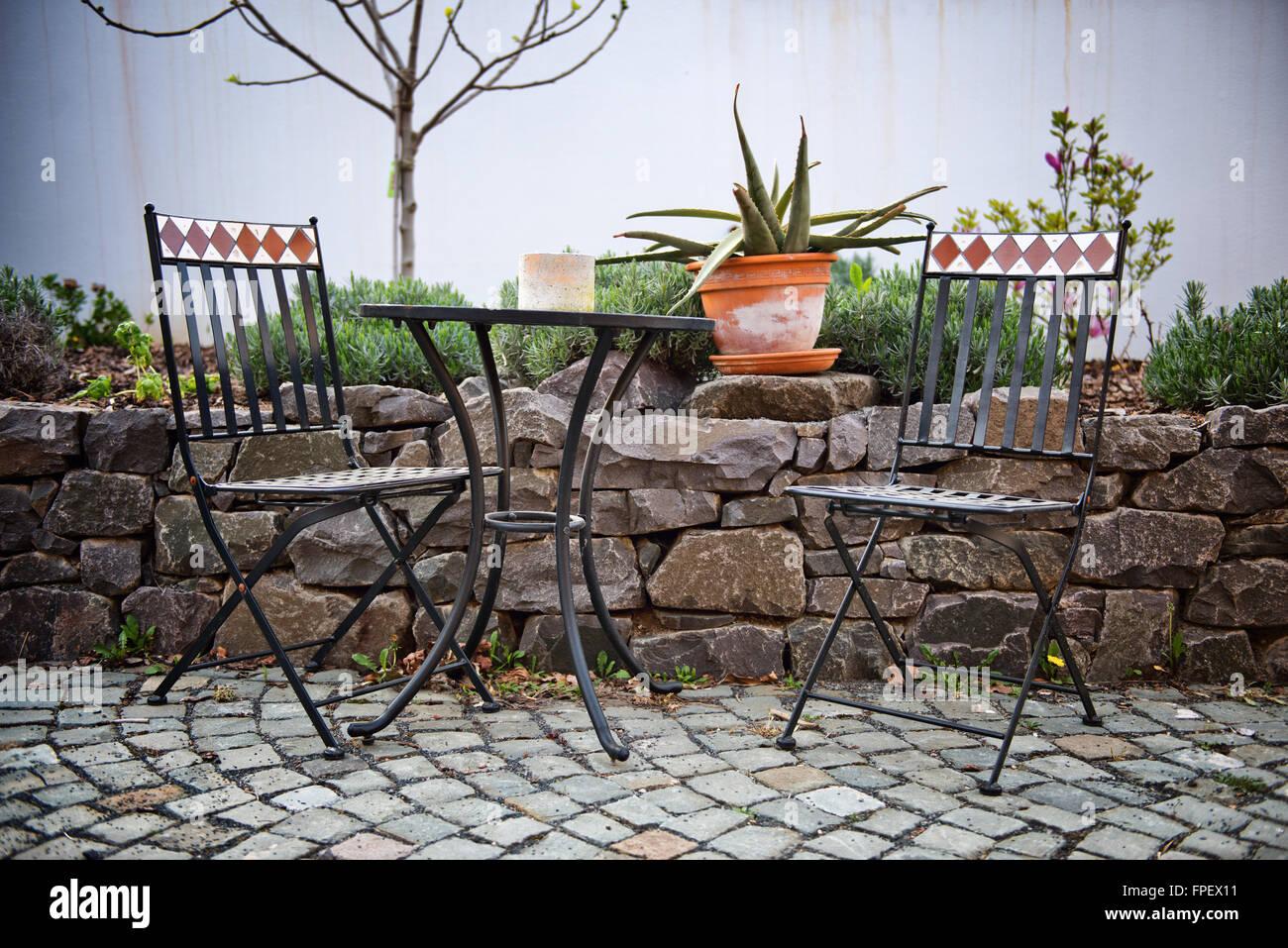Muebles de jardín de hierro fundido en un patio con una pequeña mesa ...