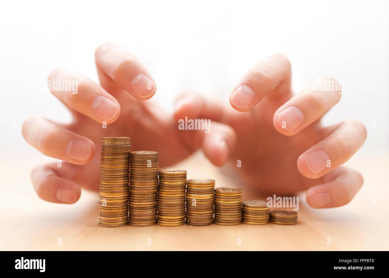 Avaricia por el dinero. Manos agarrando monedas. Foto de stock