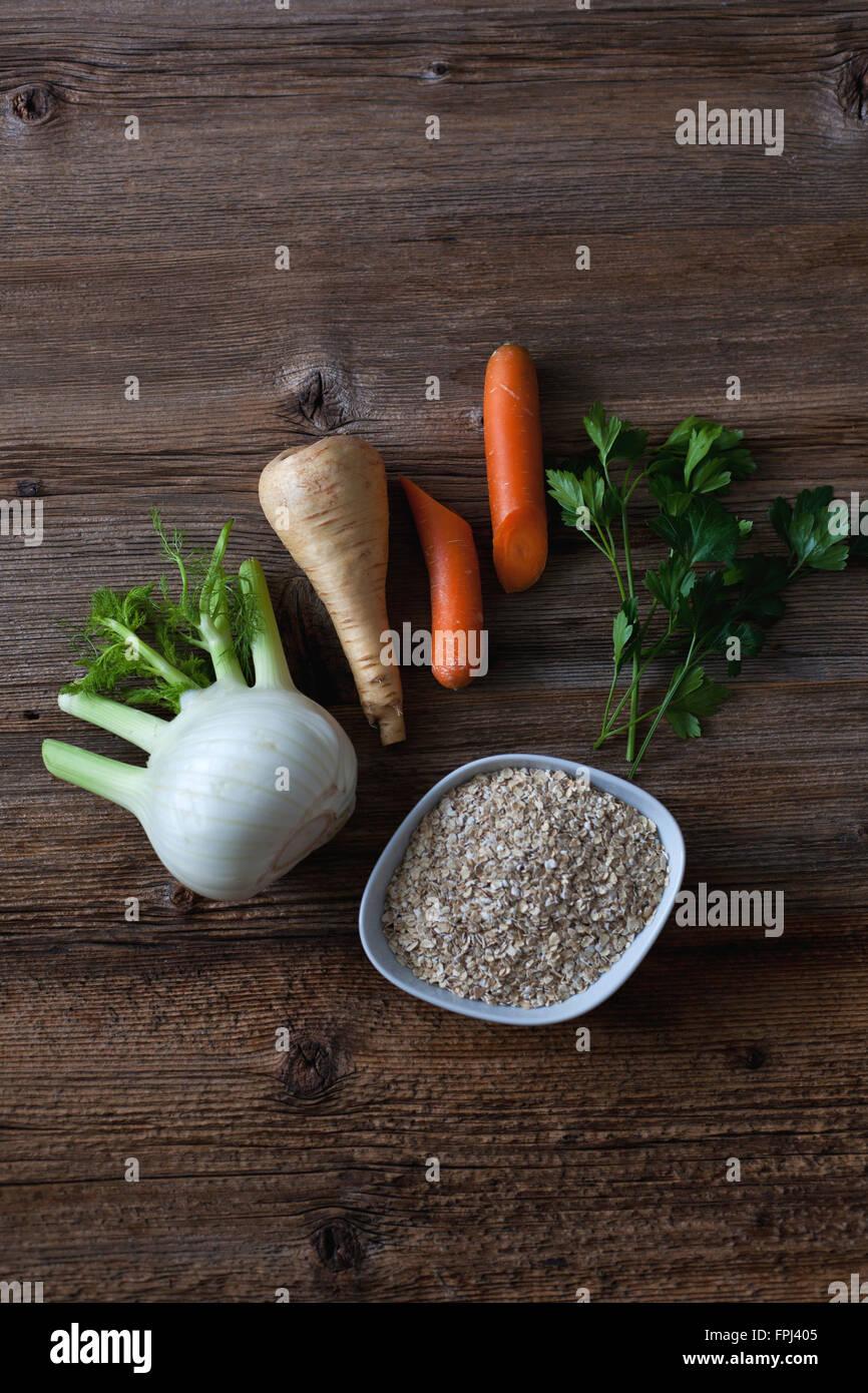 El hinojo, alcachofa, zanahoria, perejil y avena sobre la rústica mesa de madera Imagen De Stock