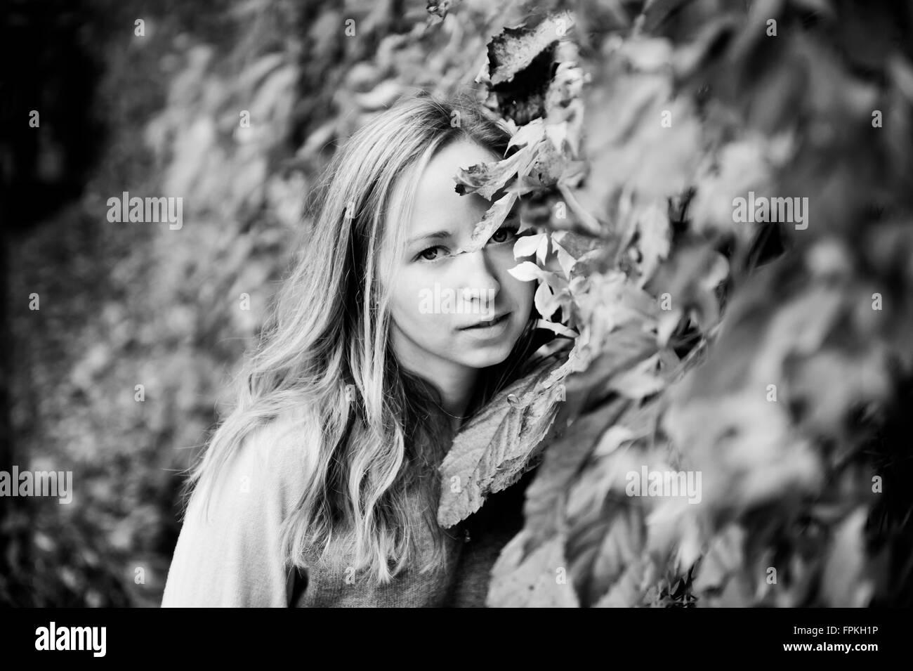 Chica que acechan a través de las hojas de otoño en blanco y negro tonation, orientación horizontal, con derechos gestionados, señor disponible. Foto de stock