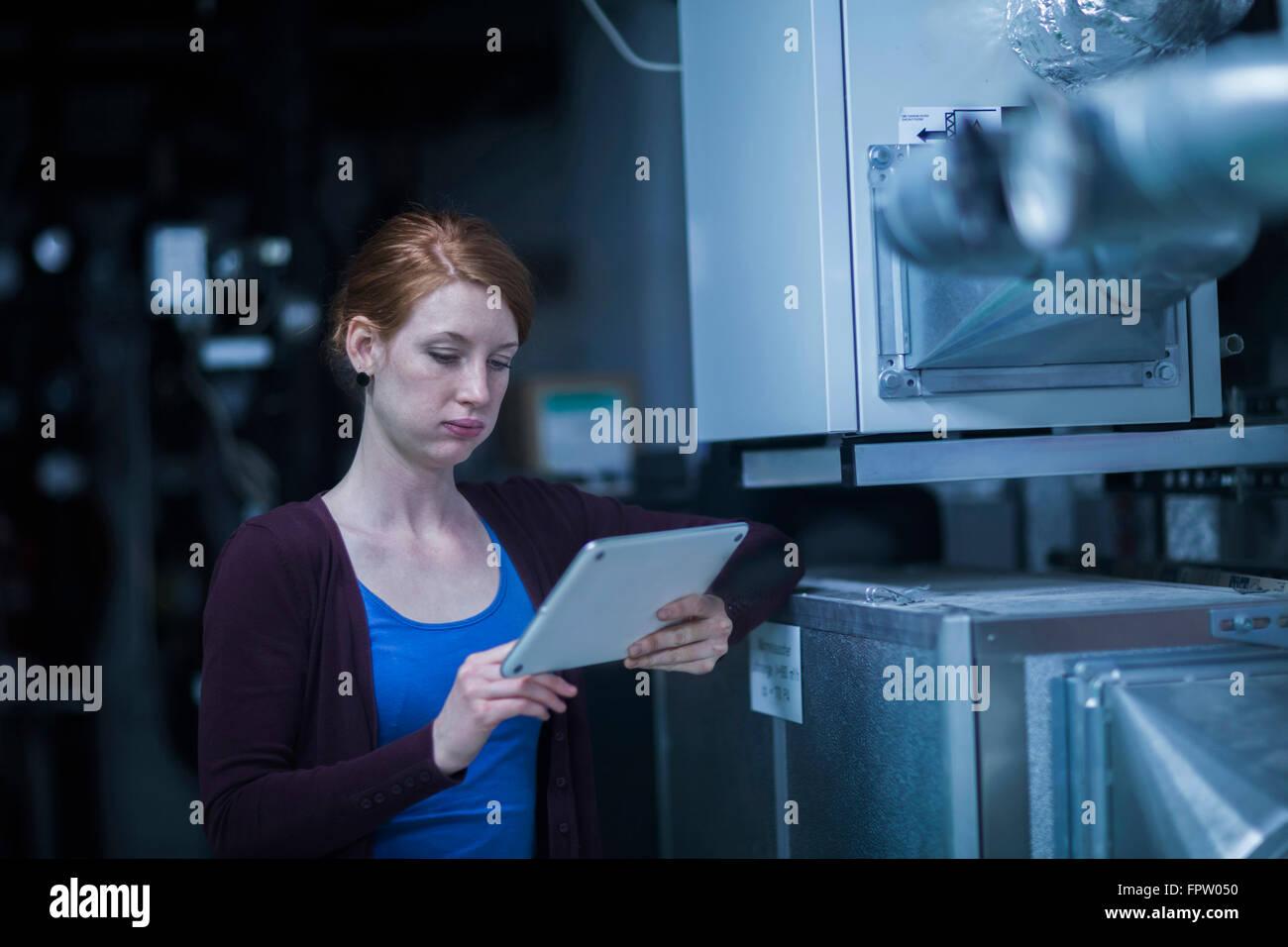 Joven ingeniero que utiliza una tableta digital en una planta industrial, Friburgo de Brisgovia, Baden-Wurtemberg, Imagen De Stock