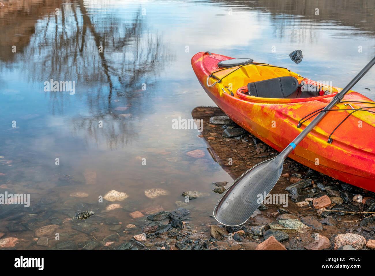 Colorido kayak de río con una paleta en la orilla rocosa con un árbol reflexión - Concepto de recreación Imagen De Stock