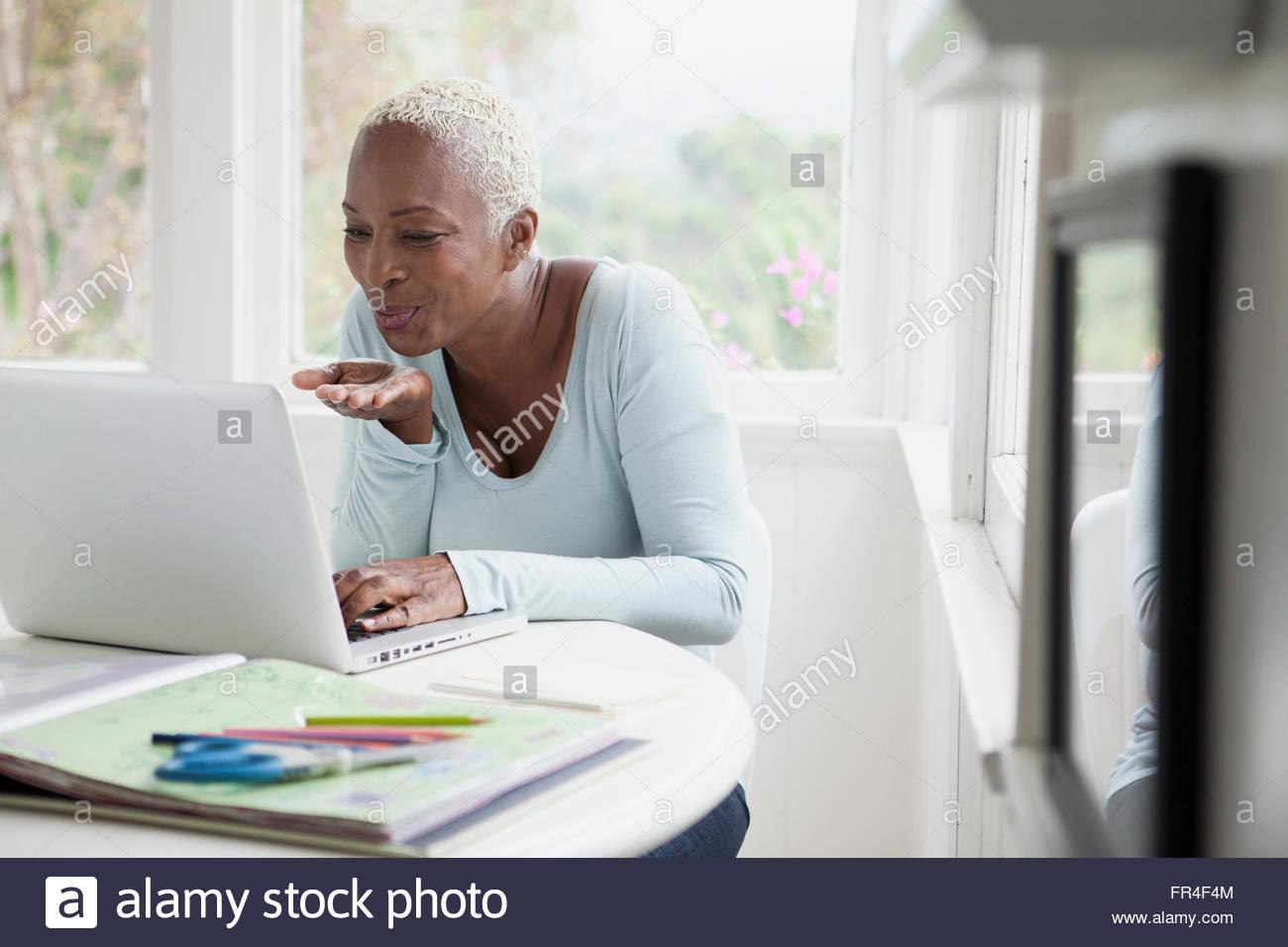Mujer de mediana edad mandando besos durante el chat en línea Imagen De Stock