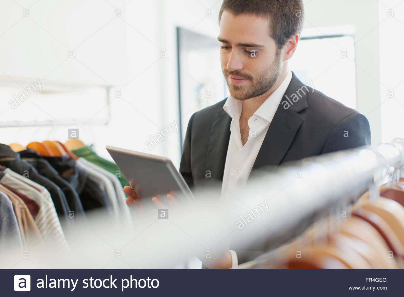El propietario de una tienda con tablet pc en mens tienda de ropa. Imagen De Stock
