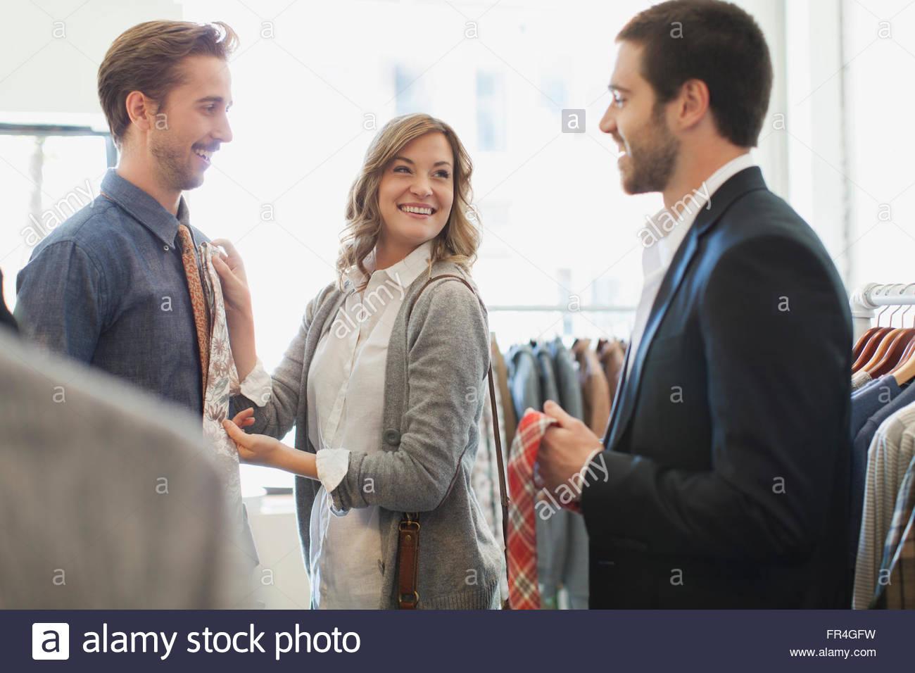 Mujer sosteniendo lazos hasta su novio en mens store. Imagen De Stock