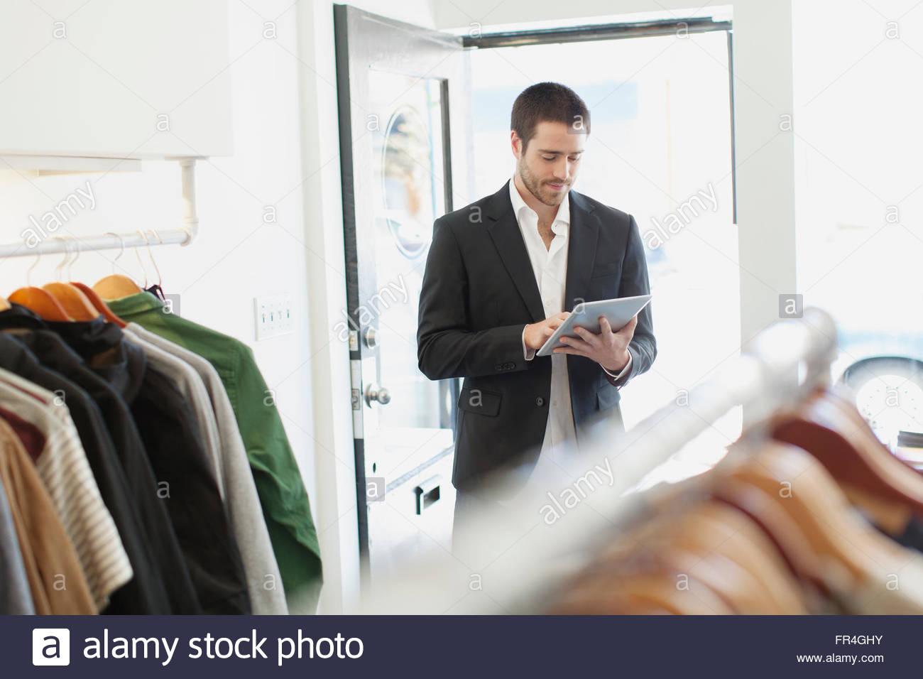 Empleado de almacén con tablet pc en mens store. Imagen De Stock