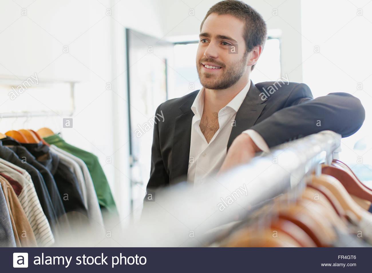 Vendedora apoyándose en rack de mens de ropa. Imagen De Stock