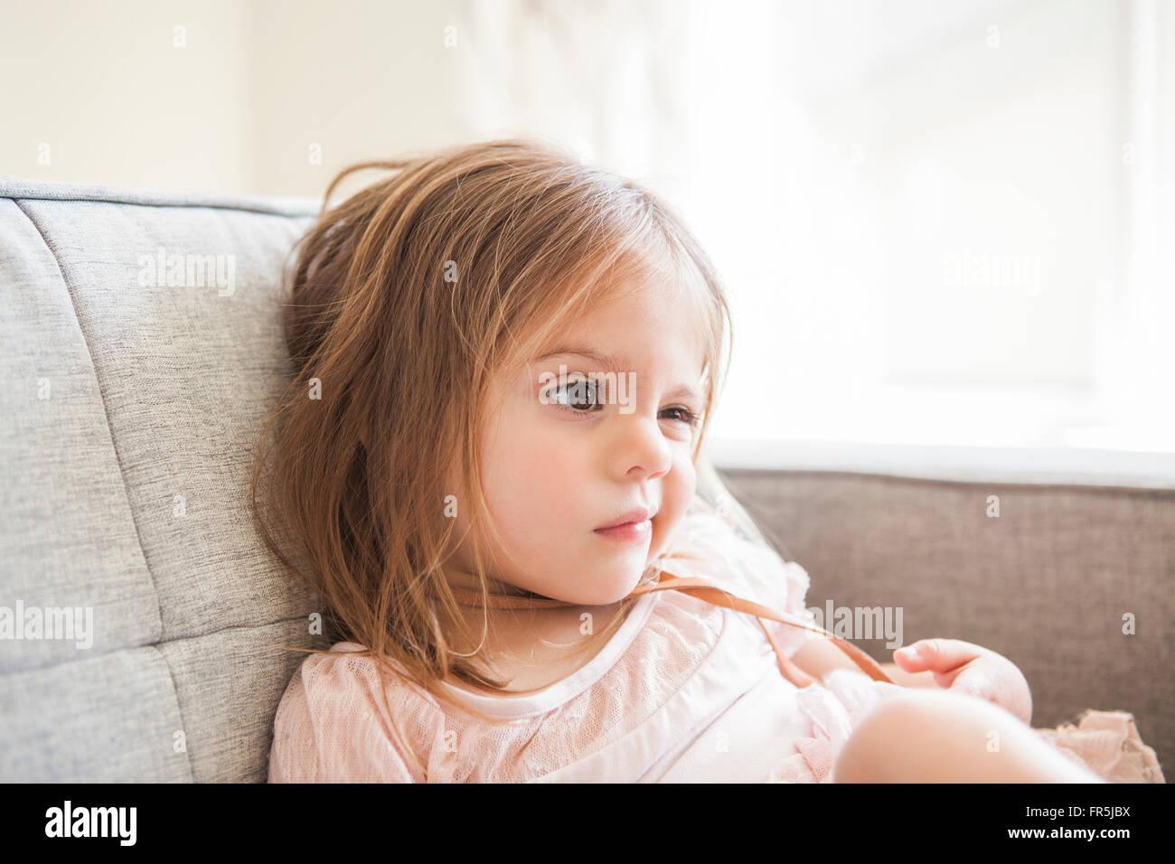 Niño Niña haciendo un rostro en el sofá Foto de stock