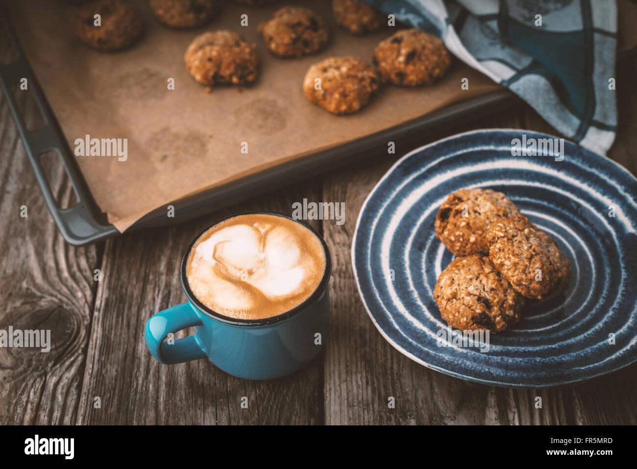 Galletas de harina de avena y la taza de café en una mesa de madera horizontales Imagen De Stock