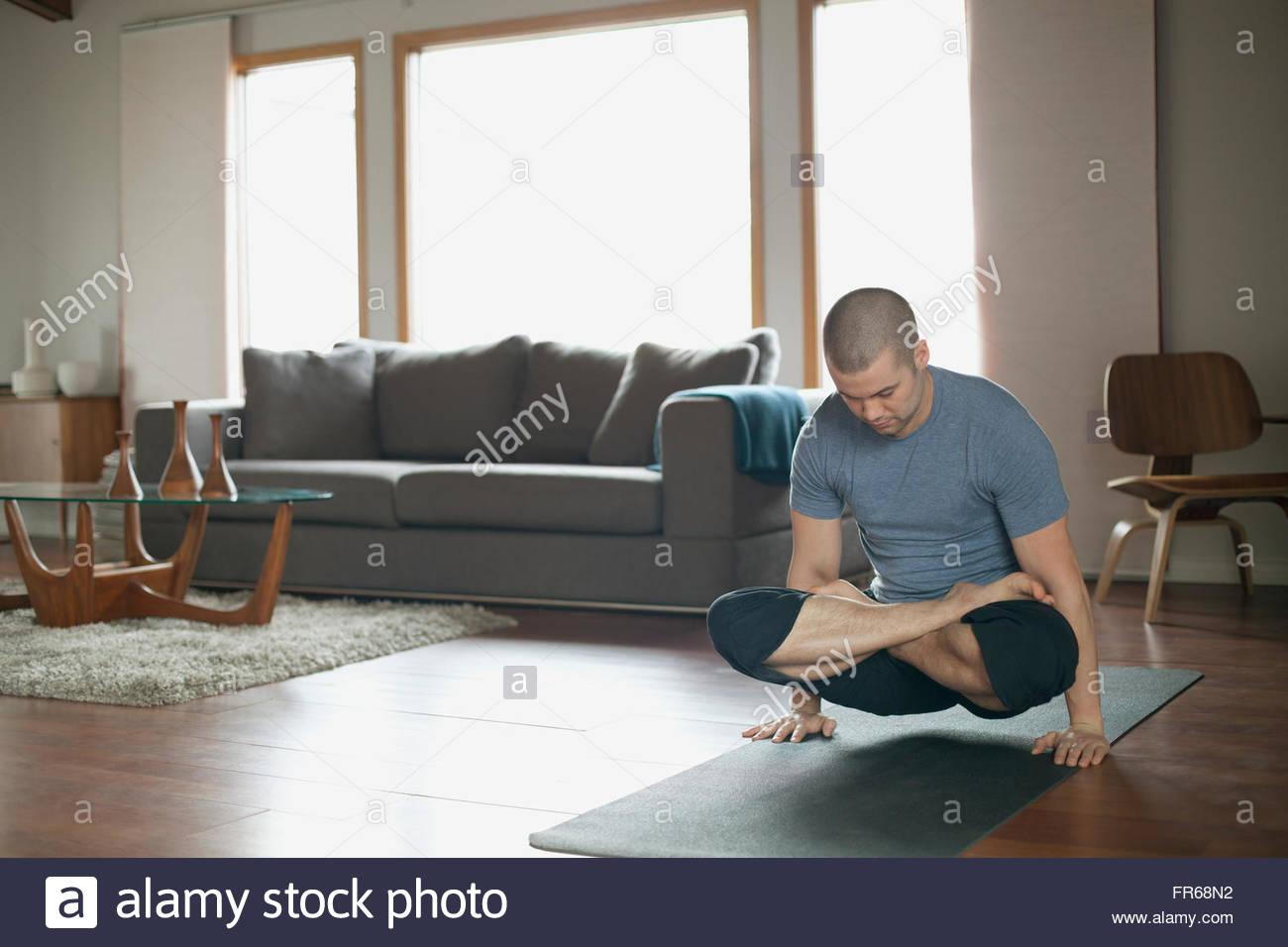 Hombre haciendo yoga plantea en casa Foto de stock
