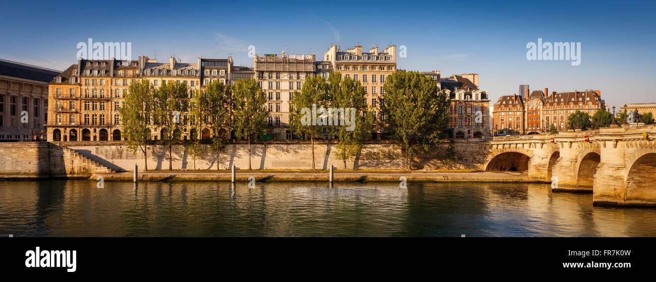 Tranquila mañana de verano a lo largo de Quai de l'Horloge en el río Sena bancos en Ile de la Cite en París, con el puente Pont Neuf Foto de stock
