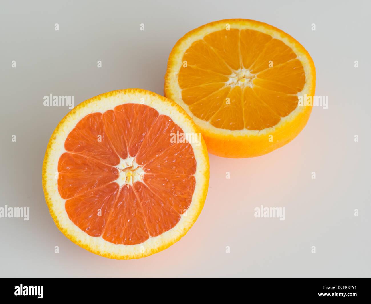 Una naranja navel cara cara (a la izquierda) en comparación con una naranja navel ordinaria (a la derecha). Imagen De Stock
