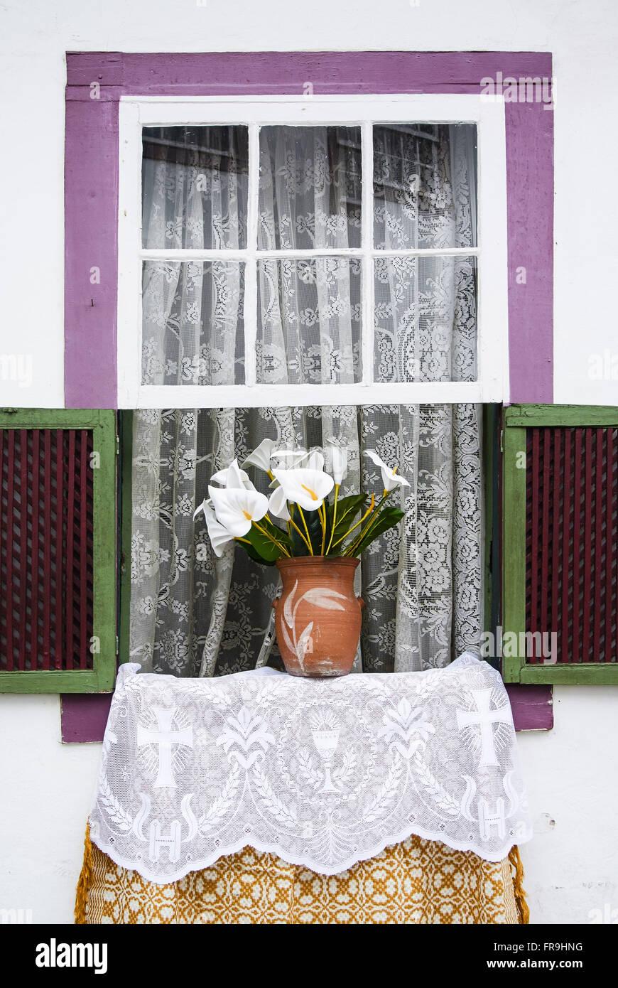 Ventana decorada con jarrón de flores para las fiestas del Corpus Christi Foto de stock