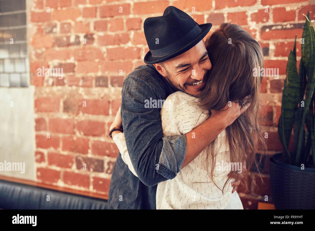 Retrato de joven abrazando a su novia en el cafe. Joven abrazando a una mujer en una cafetería. Imagen De Stock