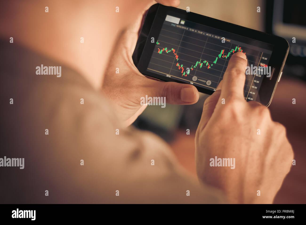 Un hombre control de stock market en smartphone Imagen De Stock