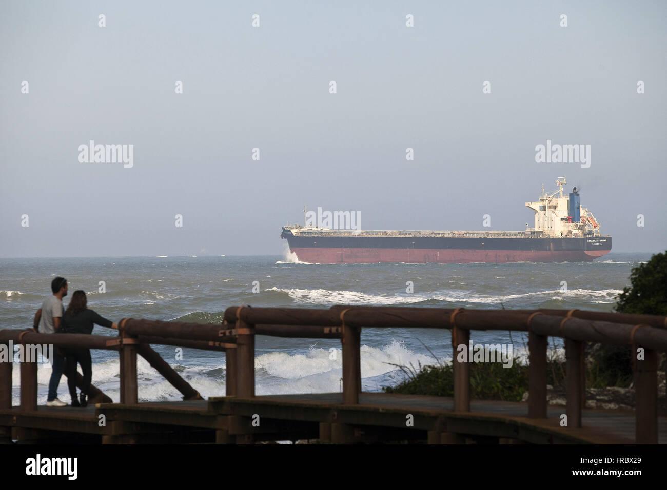 Los turistas sobre madera muelle observando la nave acercándose a la bahía de Paranaguá, en Ilha Imagen De Stock