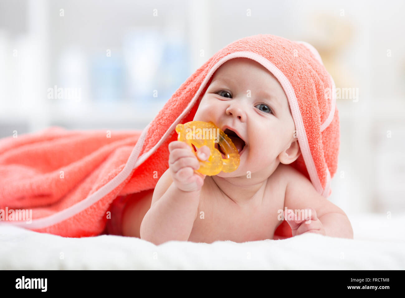 Lindo bebé con mordedor bajo una toalla con capucha después del baño Imagen De Stock