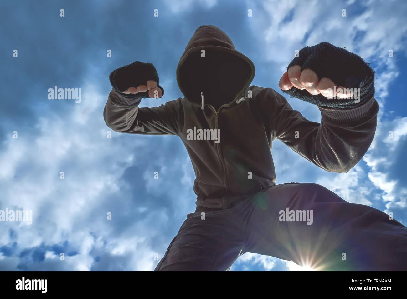 Ataque violento, hombres encapuchados irreconocible criminal víctima de patadas y golpes en la calle. Imagen De Stock