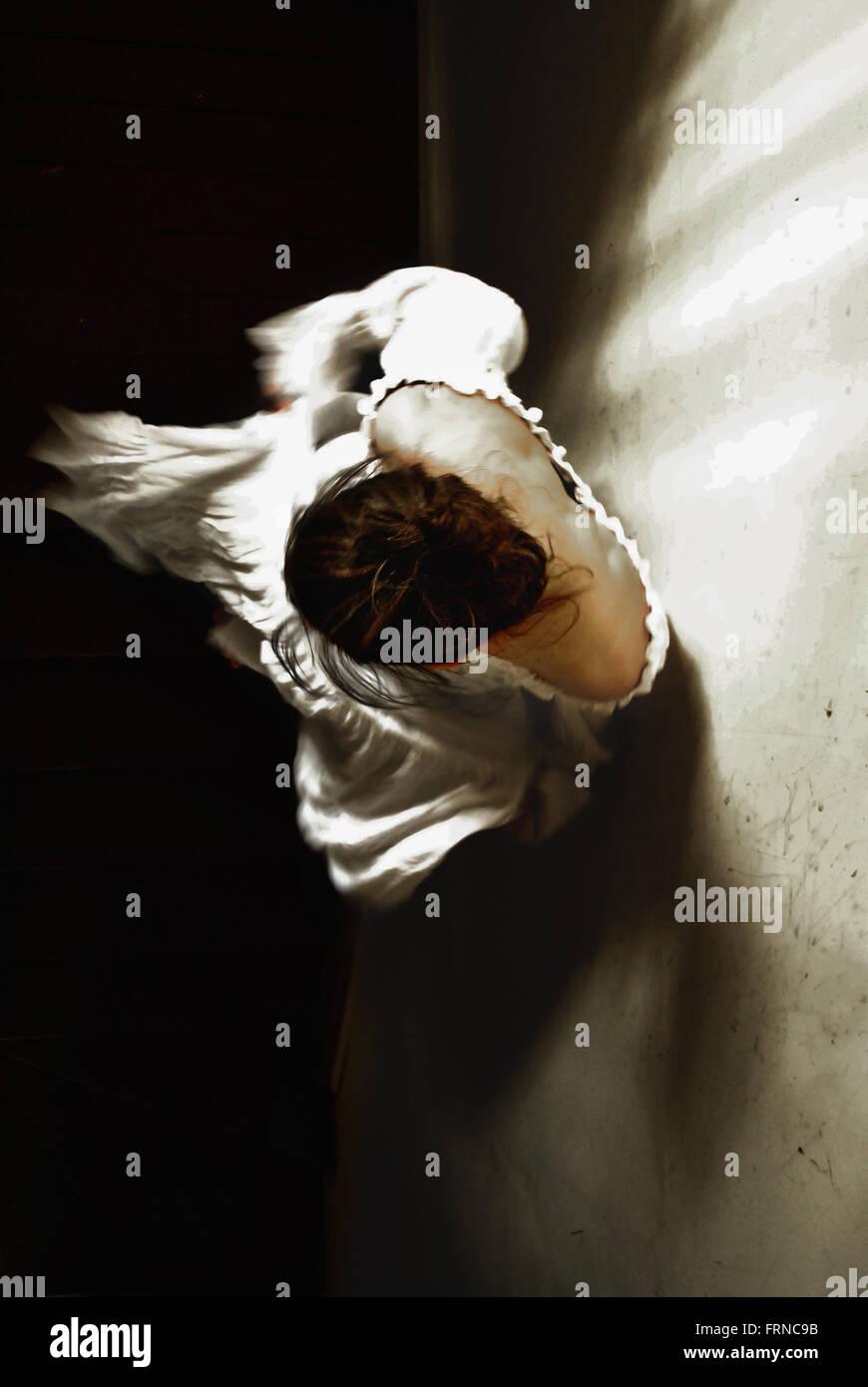 Un alto ángulo de visualización de la mujer don las escaleras en una casa antigua Imagen De Stock