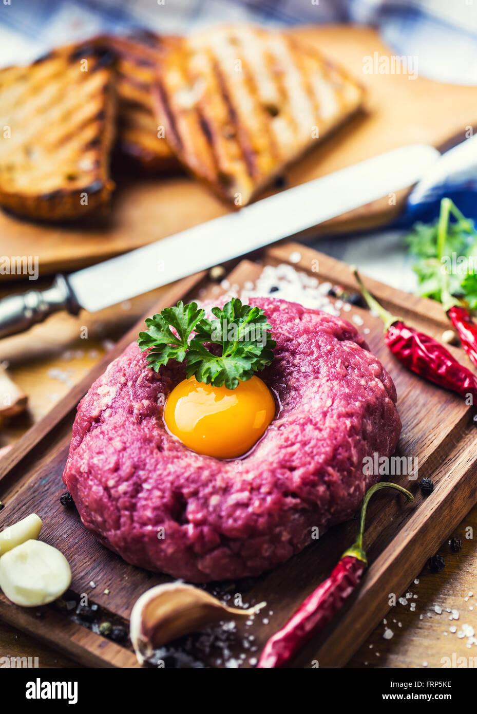 Carne cruda .sabrosa carne tártara. Carne tártara clásico sobre la plancha de madera. Ingredientes: Imagen De Stock