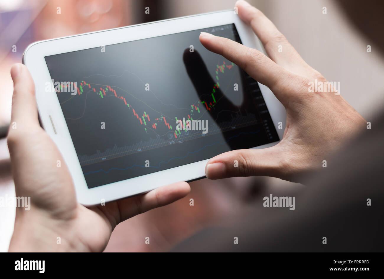 Un hombre control de stock market en tablet, smartphone Imagen De Stock
