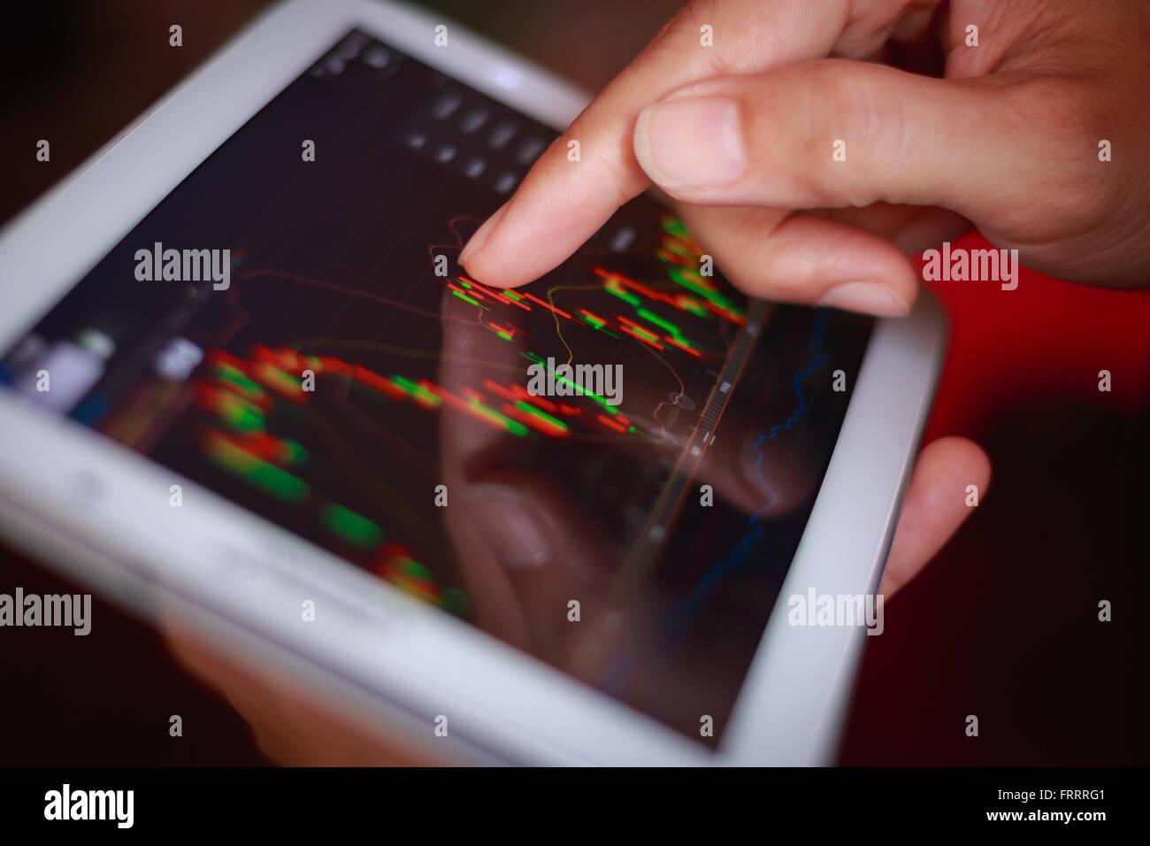 Macro de cerca un hombre control de stock market en tablet, smartphone Imagen De Stock
