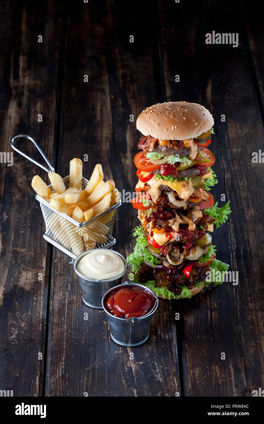 Hamburguesa extra grande con papas fritas, mayonesa y ketchup. Imagen De Stock