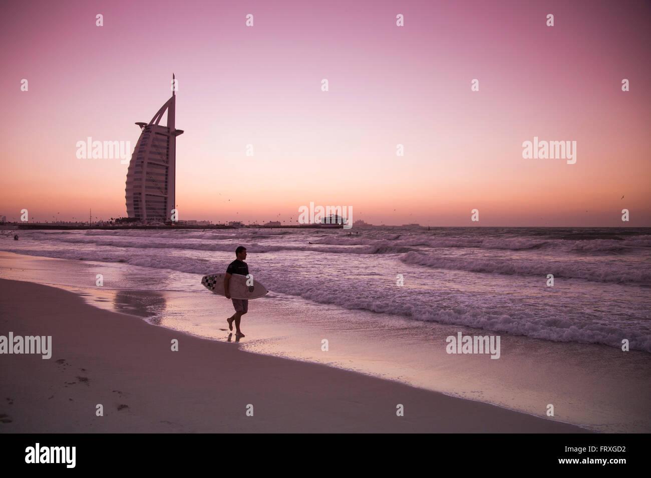 Surfer caminando por la playa cerca del hotel Burj Al Arab al atardecer, Dubai, Emiratos Árabes Unidos. Imagen De Stock