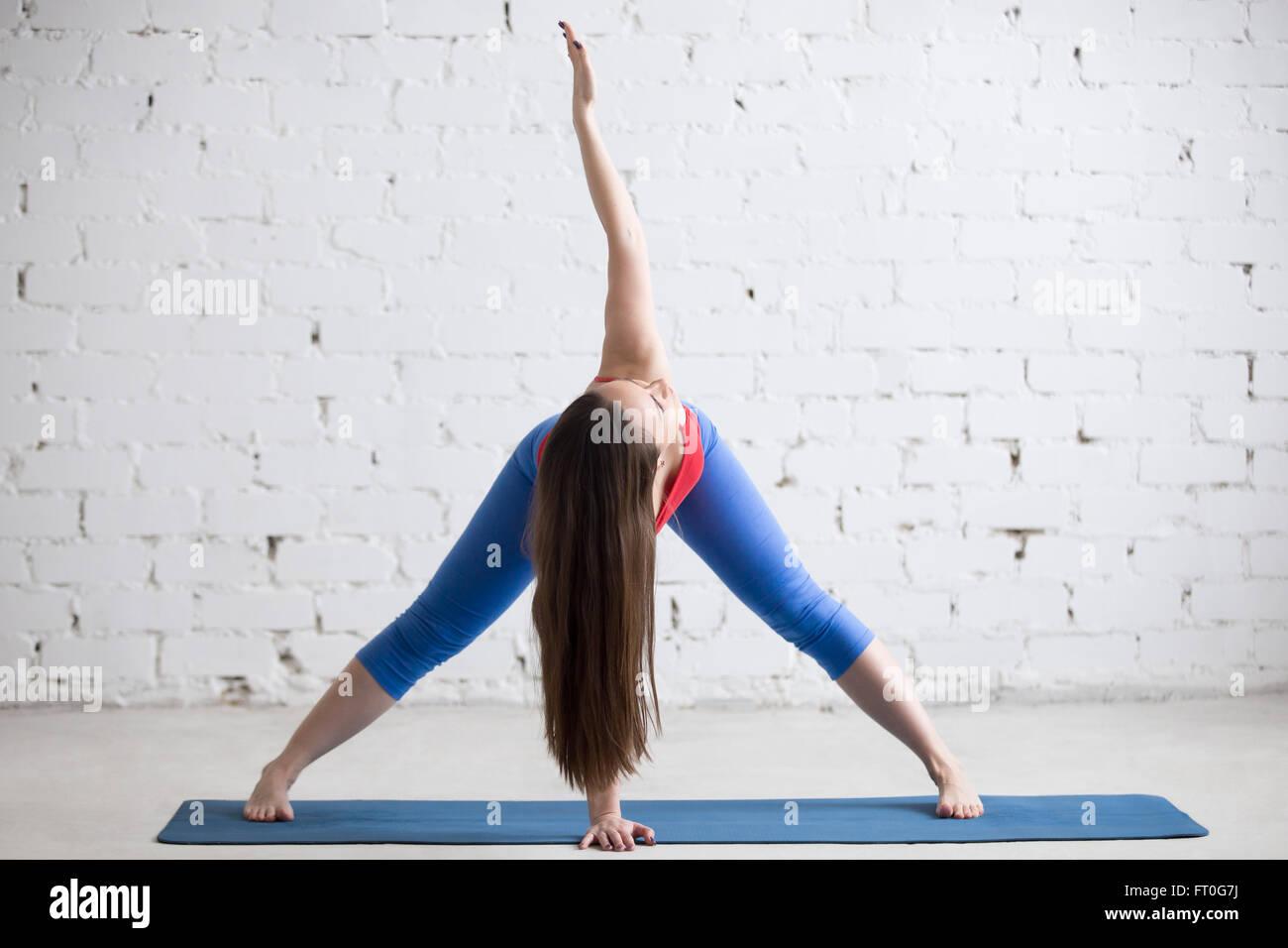 Hermosa joven en brillante colorido sportswear trabajando adentro en loft interior sobre alfombra azul Imagen De Stock