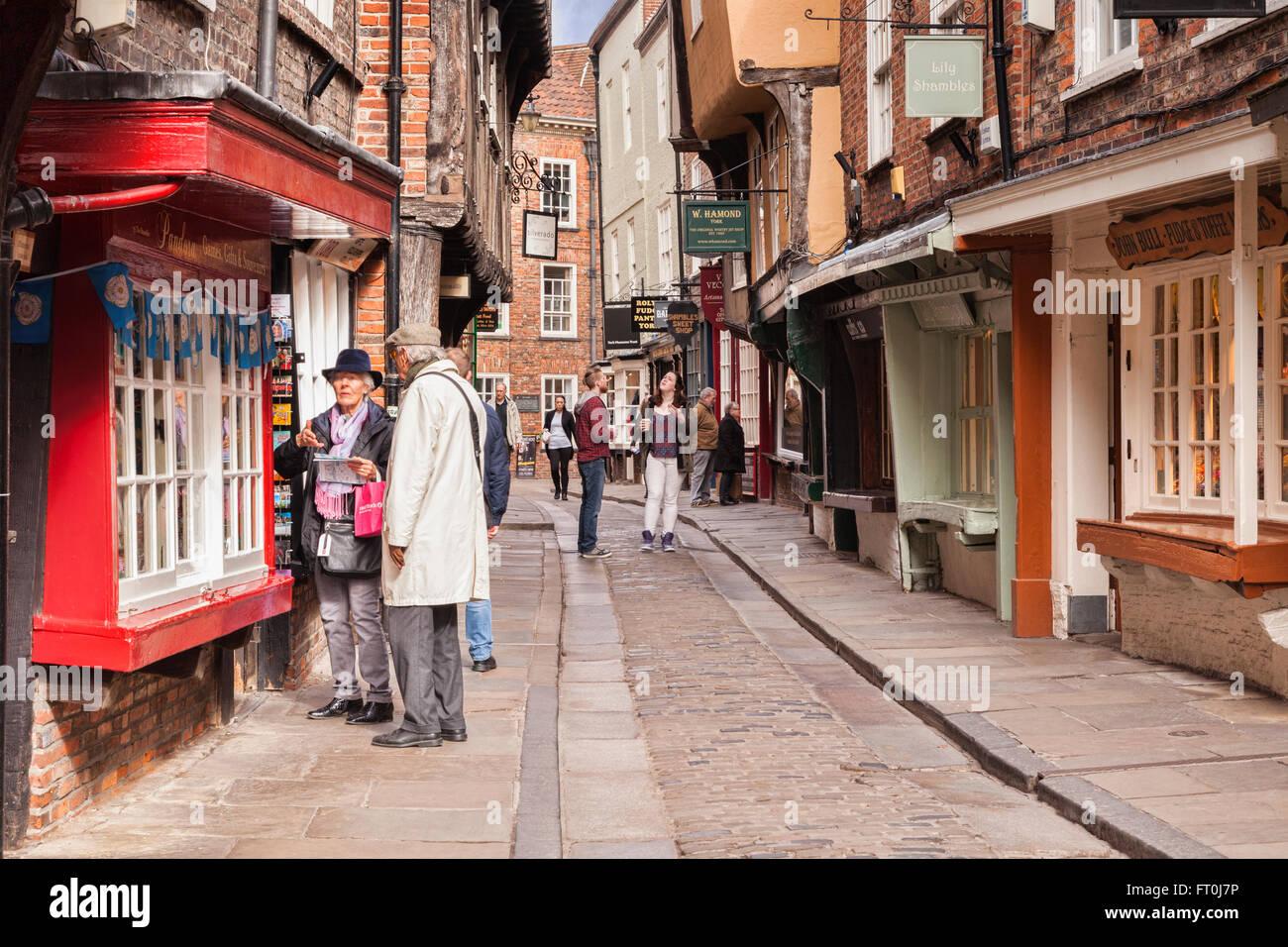 Pareja senior de compras en The Shambles, York, North Yorkshire, Inglaterra, Reino Unido ligero desenfoque de movimiento Imagen De Stock