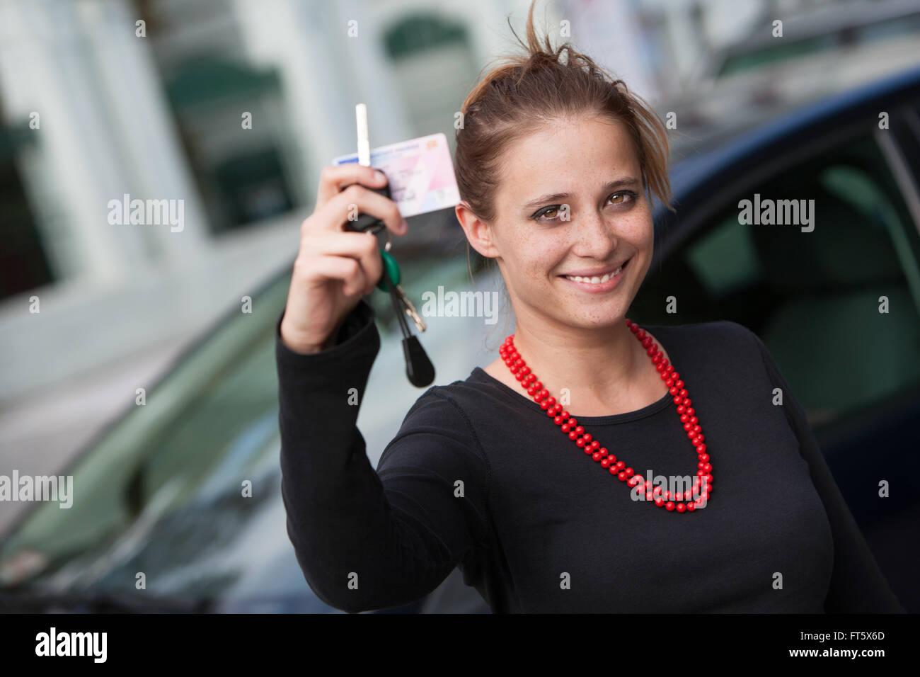 Mujer sonriente detrás del coche mostrando su licencia de conductor y claves Imagen De Stock