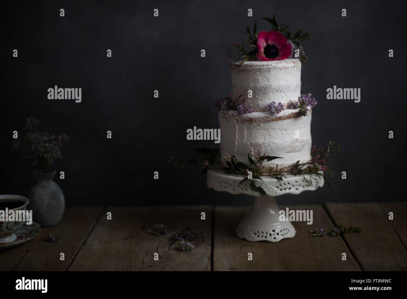 Torta casera, decoración floral, sobre un pedestal. Fondo oscuro. Imagen De Stock
