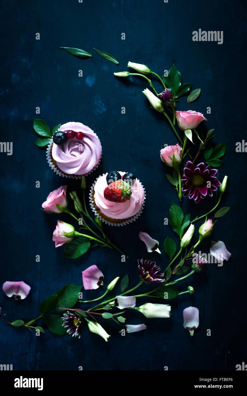 Sweet cupcakes sobre fondo de madera oscura. Imagen De Stock