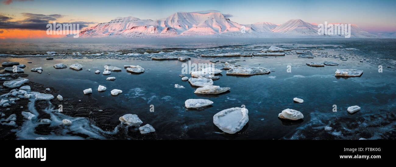 Sunset congelados en Shoreline Sjøskrenten playa con vistas a Hiorthfjellet, Longyearbyen Spitsbergen, en Svalbard. Foto de stock