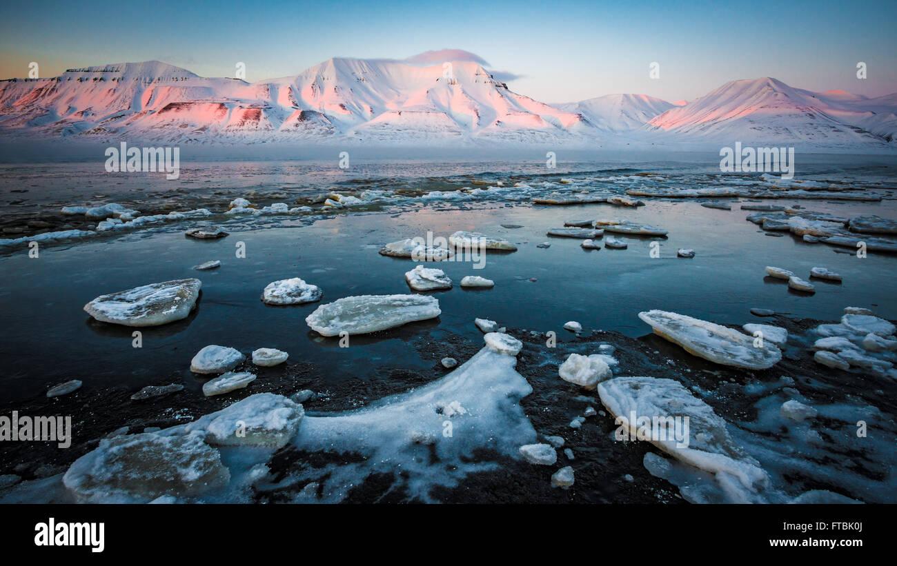 Sunset congelados en Shoreline Sjøskrenten playa con vistas a Hiorthfjellet, Longyearbyen Spitsbergen, en Svalbard. Imagen De Stock