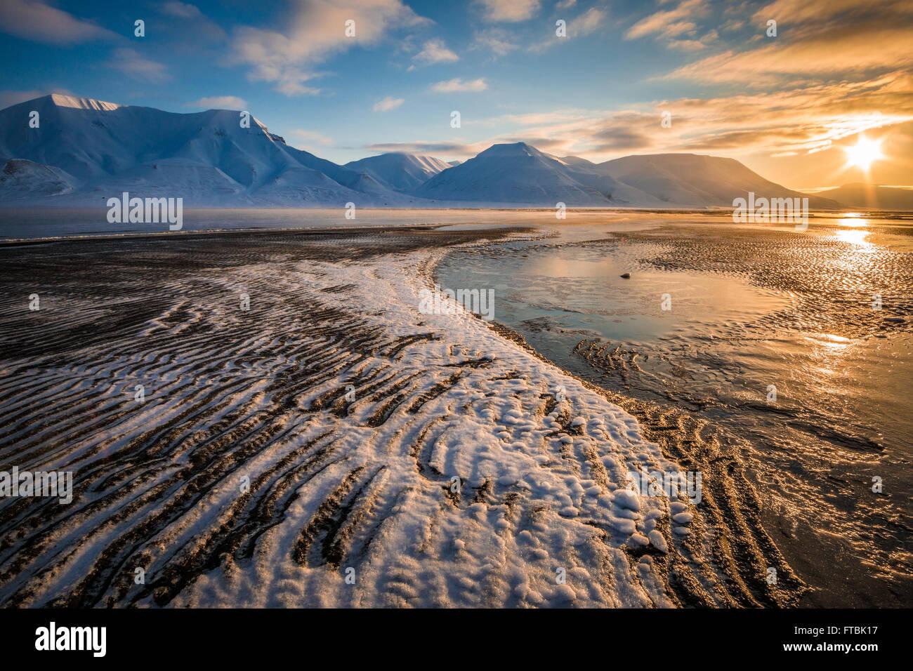 Formaciones de hielo sobre Sjøskrenten Sunrise Beach con vistas a Hiorthfjellet, Longyearbyen Spitsbergen, en Svalbard. Foto de stock