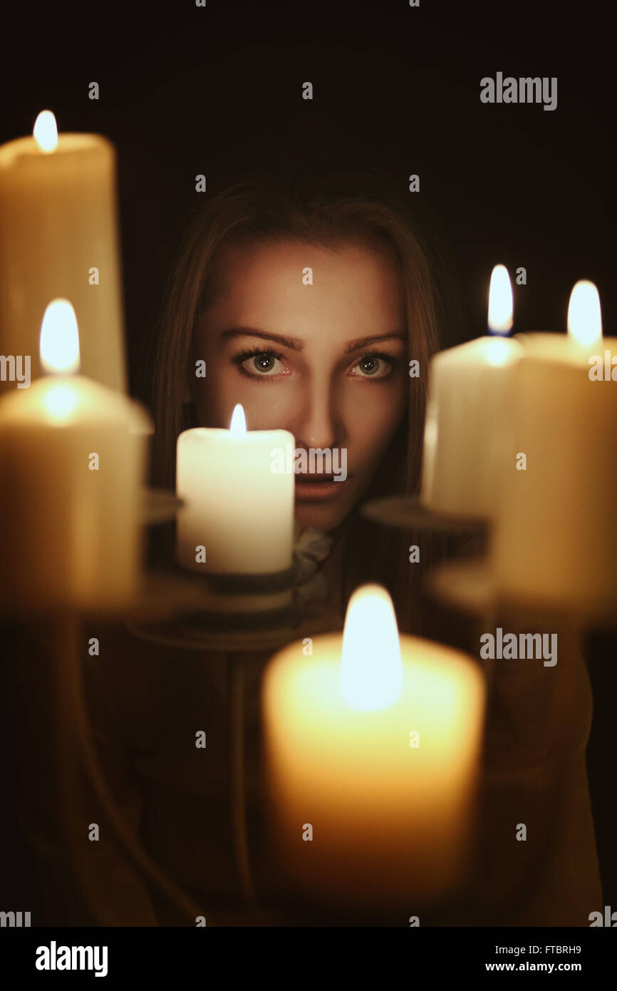 Velas oscuro retrato de una joven mujer . Gótico y el concepto surrealista Foto de stock